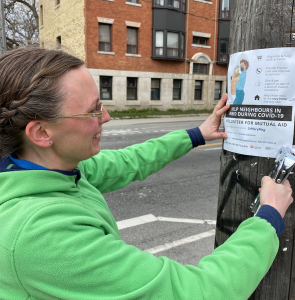 volunteer posters her neighbourhood for mutual aid