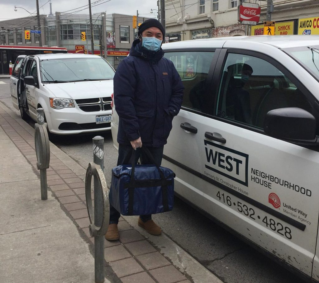 staff member delivers meals on wheels using PPE