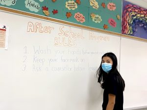 """After school program worker in a mask stands in front of a whiteboard that says """"After School program rules: Wash your hands before and after you eat and after you enter, keep your face mask on, see a counsellor before leaving"""""""