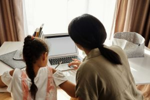 A mother helps her daughter with her homework on a computer screen.