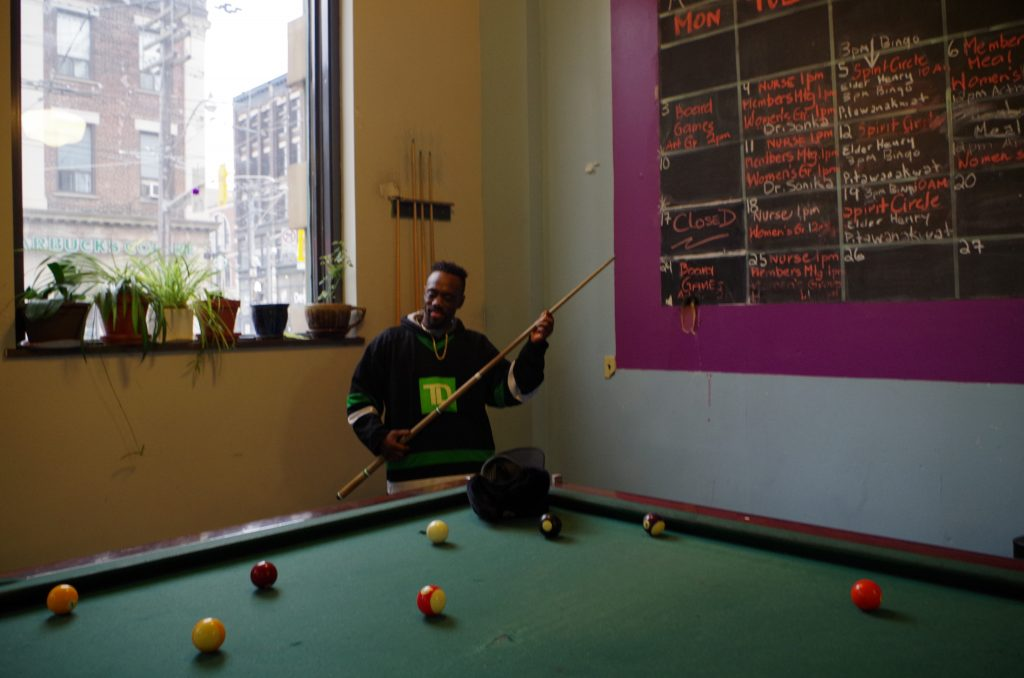 A participant plays pool at the Meeting Place in front of a schedule of activities